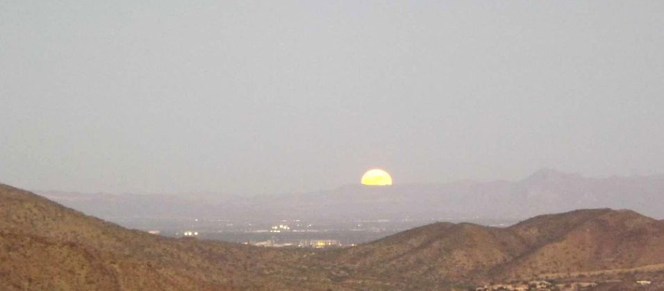 Full moon rising over desert hills
