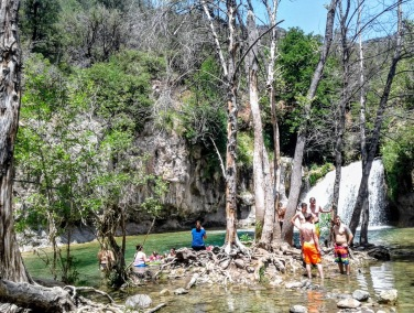 People wading in the pools beneath Fossil Creek waterfall
