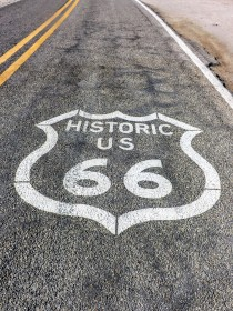 Route 66 sign on asphalt highway in front of Cold Springs Station
