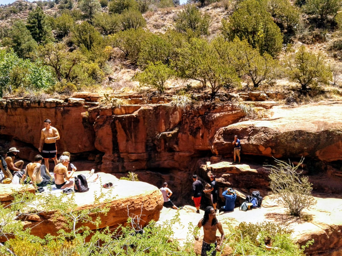 People lounging around on large platforms of red rock separated by a creek