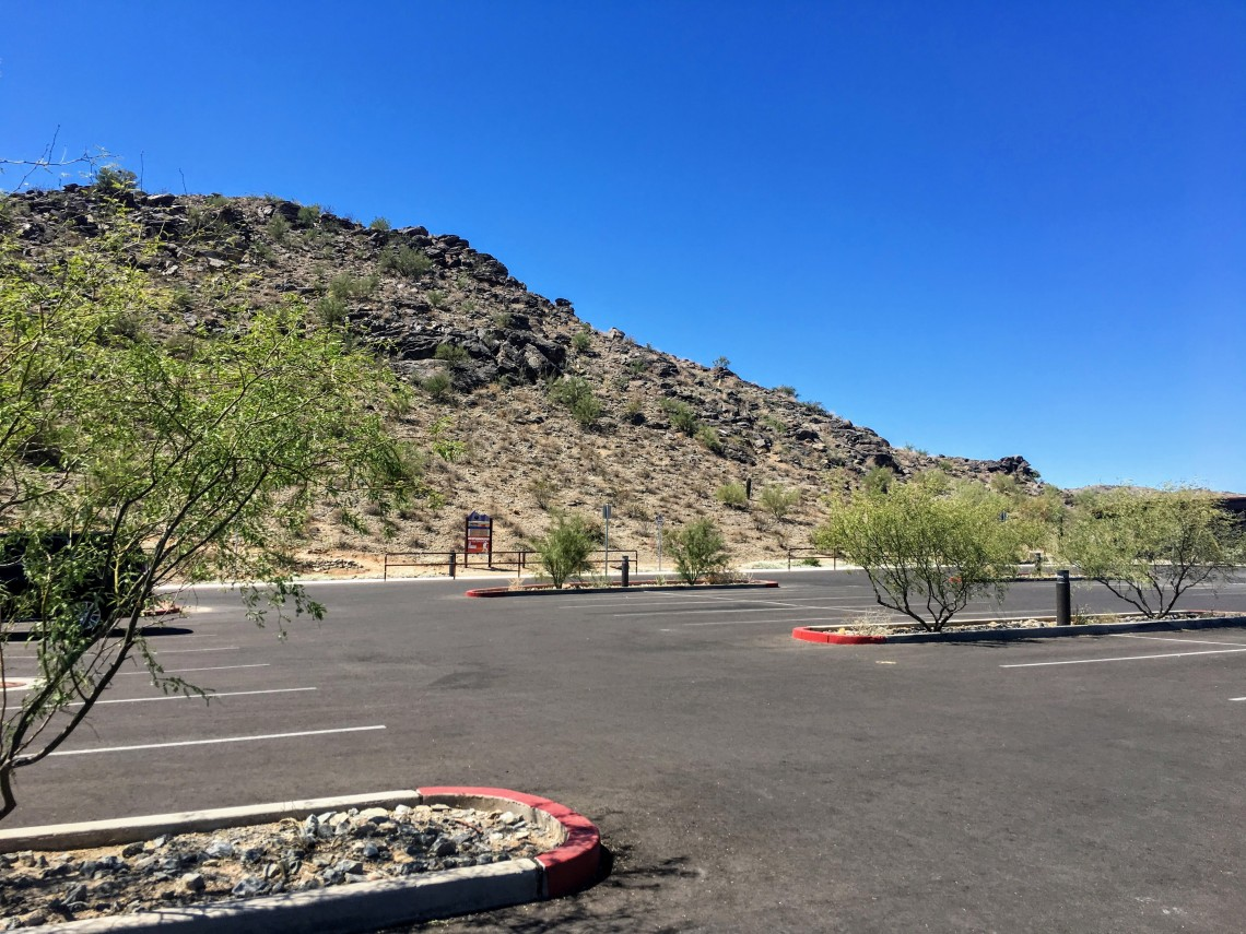 empty parking lot with desert mountain rising in background