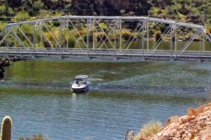 Motorboat passes under bridge as it exits cove